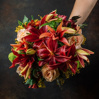 Burgundy and orange lillian bouquet with roses in dark background
