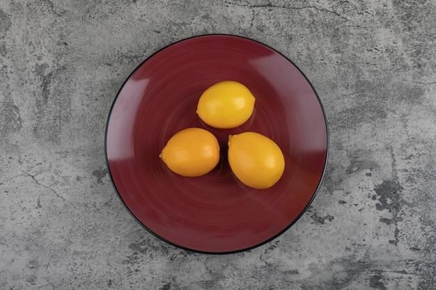 Burgundy plate and fresh juicy lemons on stone table.