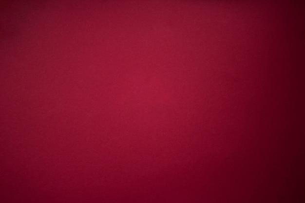 ブルゴーニュの赤い縞模様の紙のテクスチャの背景。暗い斑点のある紫赤グランジ壁の背景。