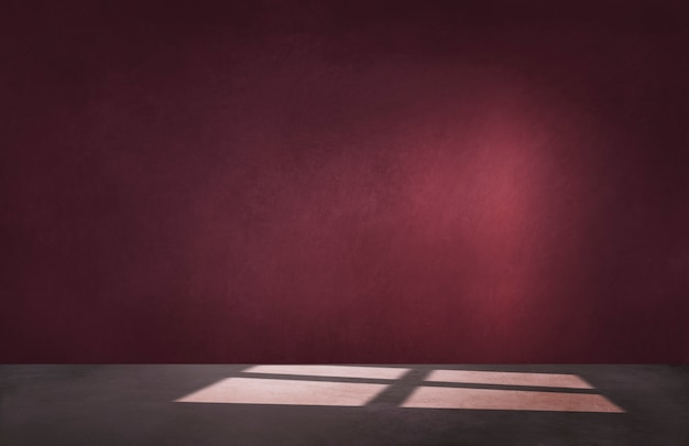 Burgundy red wall in an empty room with concrete floor