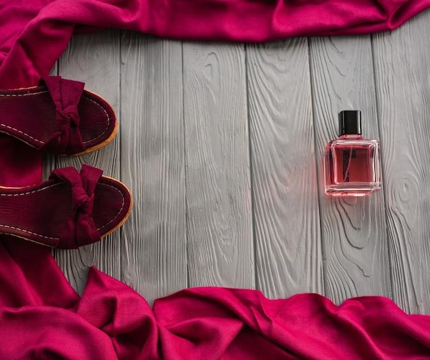 バーガンディサンダルウェッジショールシューズとボトルピンクの香水。
