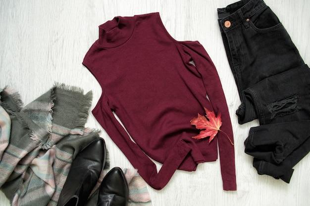 ブルゴーニュのトップス、スカーフ、ブラックジーンズ、ブーツ。ファッショナブルなコンセプト