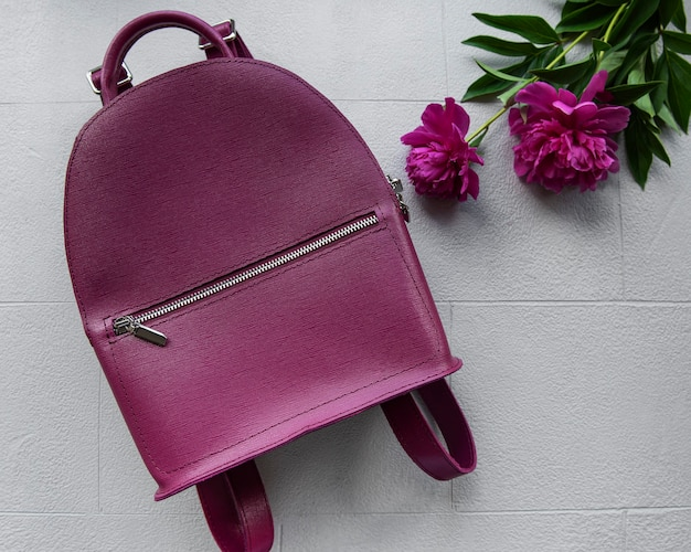 Burgundy women's backpack  on grey tile, top view. stylish accessory