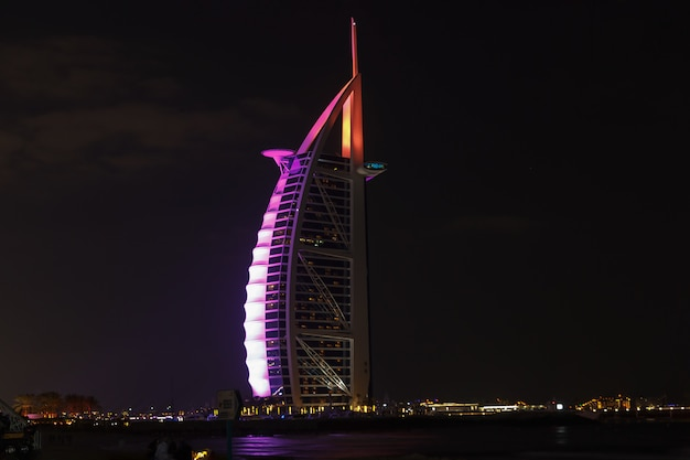 The burj el arab hotel at night on jumeirah beach.