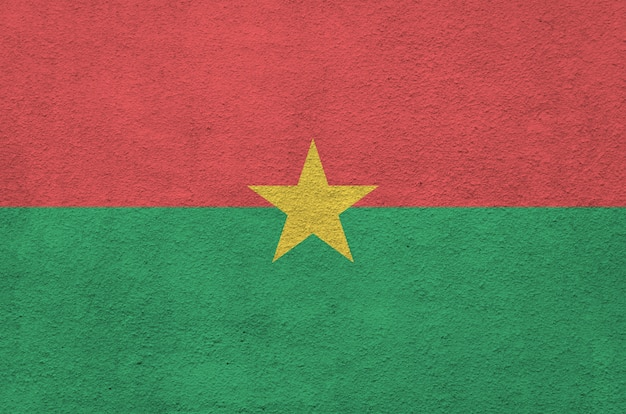Burkina faso flag depicted in bright paint colors on old relief plastering wall.