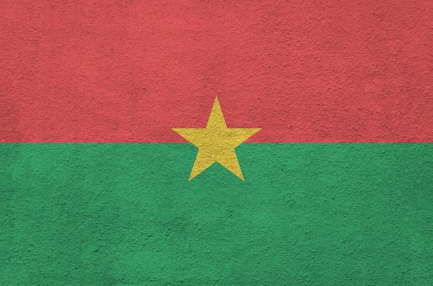 古いレリーフの左官壁に明るいペンキ色で描かれたブルキナファソの旗。