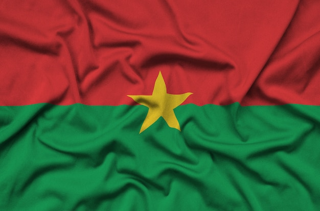 Burkina faso flag is depicted on a sports cloth fabric with many folds.