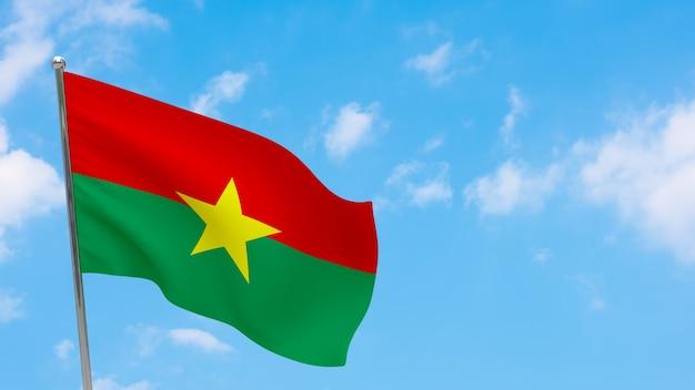 Флаг буркина-фасо на шесте. голубое небо. государственный флаг буркина-фасо