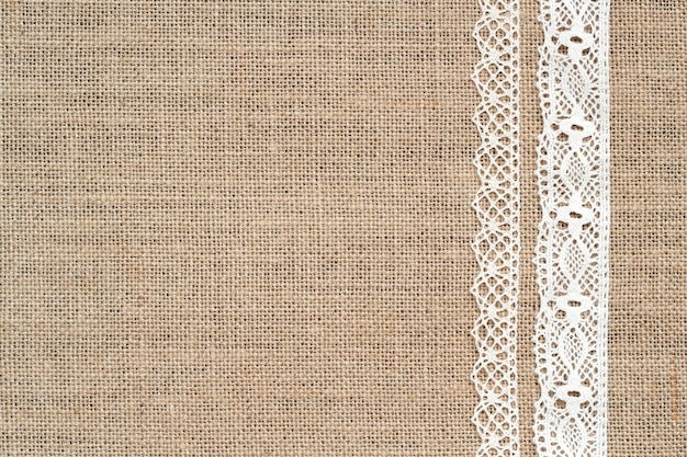 Burlap background with lace border top view