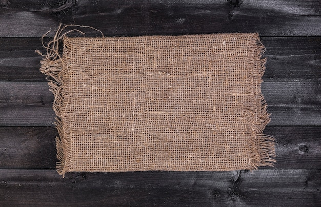 Burlap on black wooden, top view