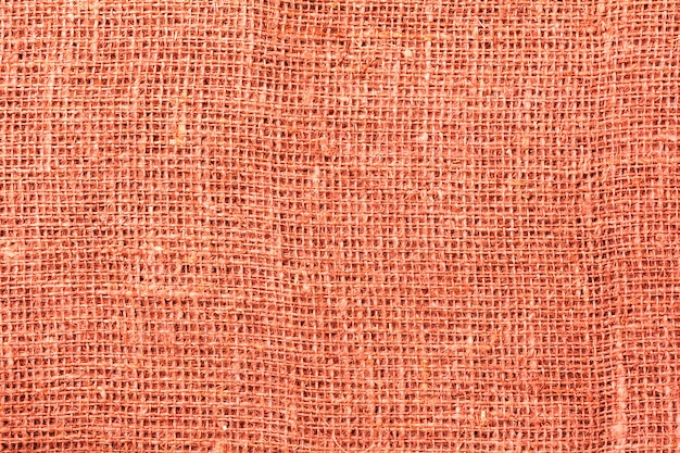 Burlap, canvas fabric texture background. trendy living coral color of year 2019. zero waste concept. top view. copy space.