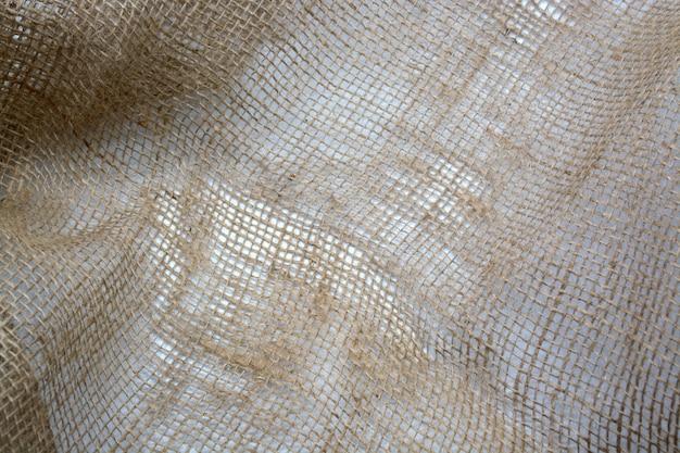 Мешковина мятой текстуры фона коричневый тканые крупным планом