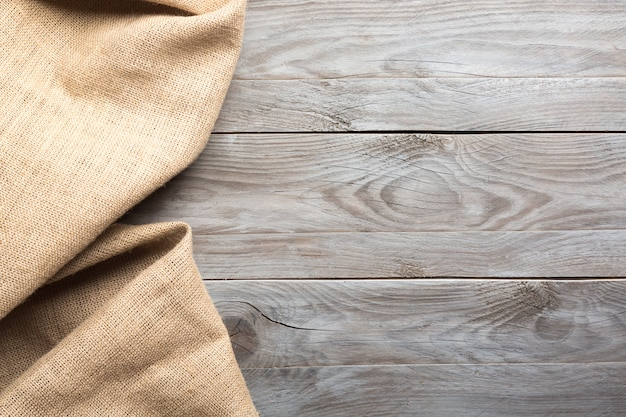 Burlap hessian sacking cloth on wooden table background with free space.