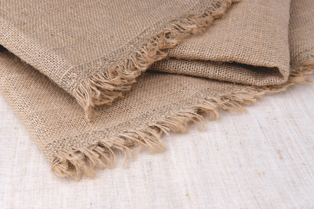 Burlap is spread on a light bedspread. a fringe of fine threads along the edge of dense material. thick canvas for diy products.