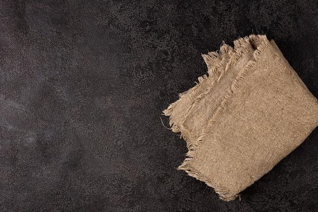 Burlap napkin on a dark structural background top view copyspace