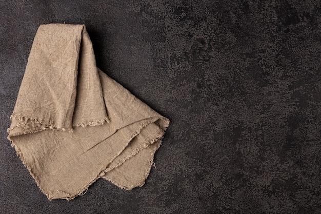 Burlap napkin on a dark structural background, top view. copyspace