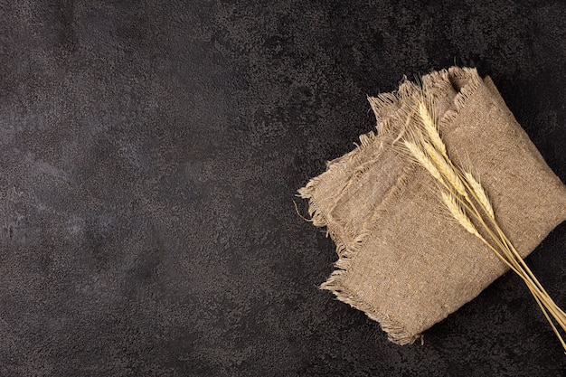 Burlap napkin on a dark structural background, top view. ears of wheat. copyspace