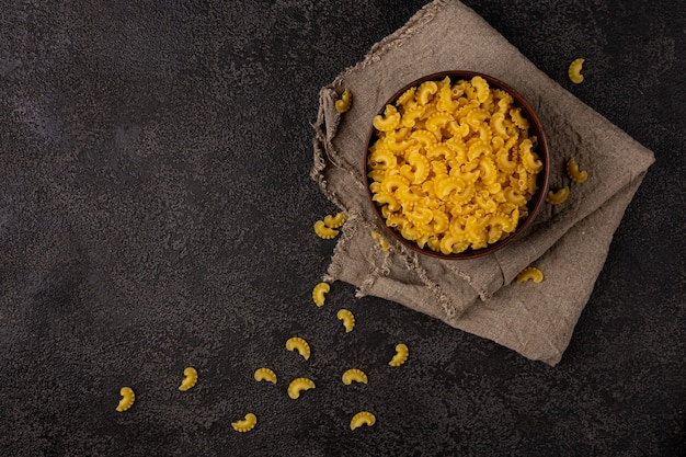 Burlap napkin on a dark structural background, top view. it has raw macaroni in a black bowl copyspace