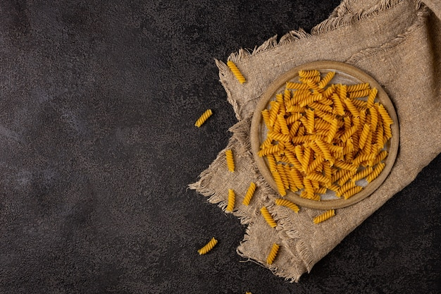 Burlap napkin on a dark structural background top view on it is a scattering of pasta in a ceramic plate copyspace
