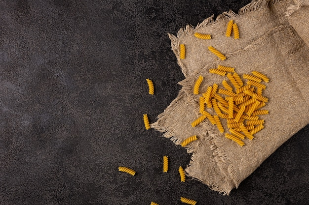 Burlap napkin on a dark structural background top view a scattering of macaroni on it copyspace