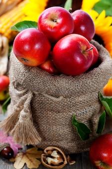 木製のテーブルにリンゴと黄麻布の袋