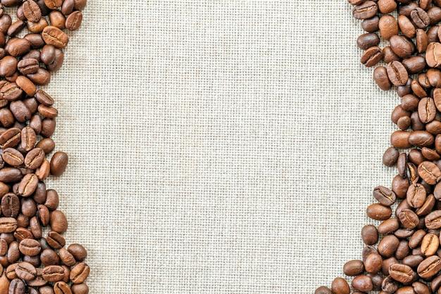 黄麻布のキャンバスとコーヒー豆は写真の背景に配置されます。コピースペース。コーヒーボーダー