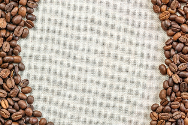 Burlap sackcloth canvas and coffee beans placed round photo background. copy space. coffee border