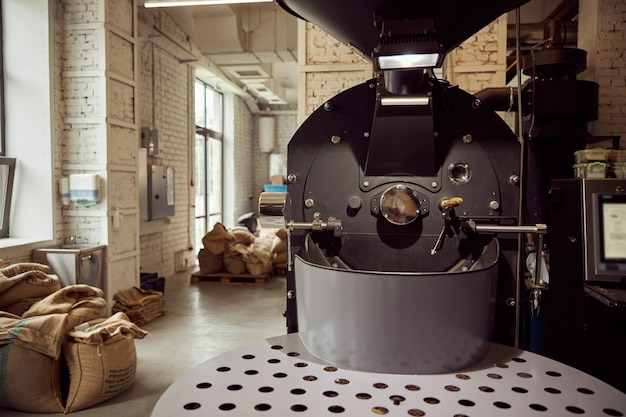Burlap sacks with coffee beans and professional equipment for roasting at factory