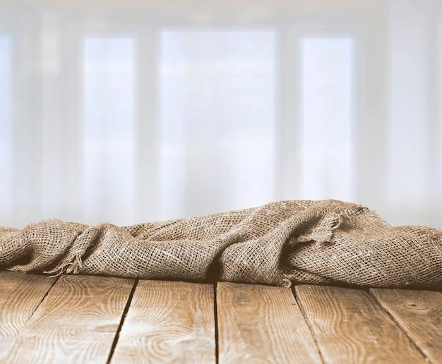 ぼやけた木のテーブルの黄麻布のテクスチャ