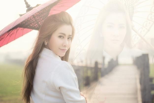 伝統的な赤い傘を持ってu-bein橋を歩いているビルマの女性