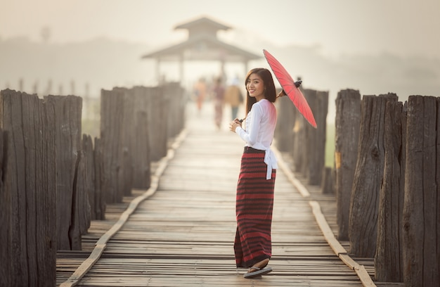 Burmese woman holding traditional red umbrella and walking on u bein bridge, myanmar
