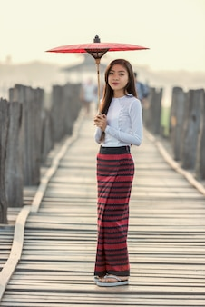 Burmese woman holding traditional red umbrella and walking on u bein bridge, myanmar