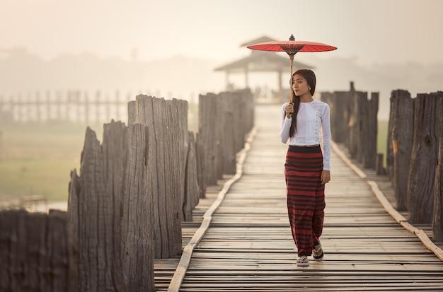 Burmese woman holding traditional red umbrella and walking on u bein bridge