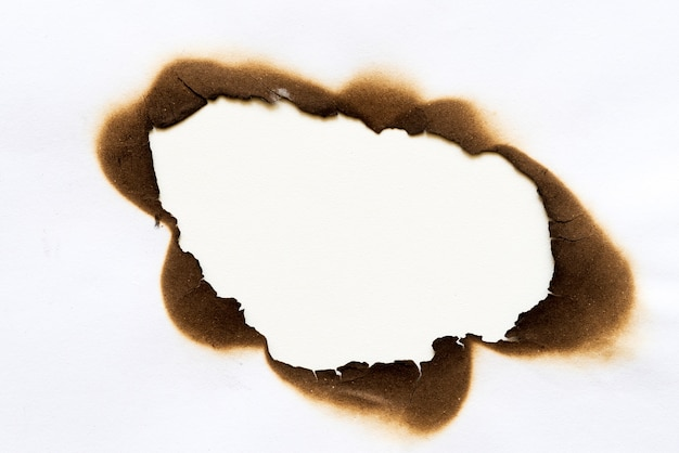Burned hole on piece of paper isolated on white background