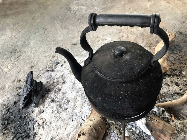 Burned thai vintage black hot teapot on fire charcoals wood.