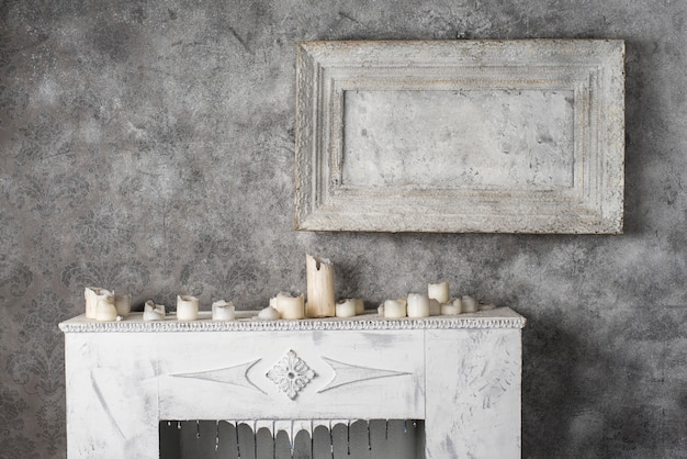 Burned wax candles on the old fireplace
