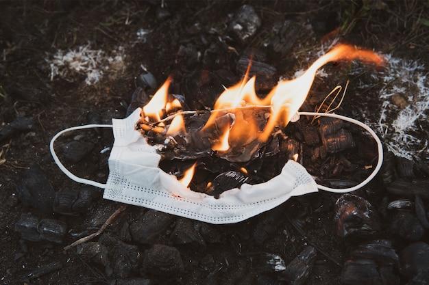 Горящая медицинская маска, хирургическая маска с очищающим обеззараживанием огня. концепция конца пандемии коронавируса. сжигание уничтожения защитной маски для лица. загрязнение природы масками