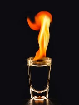 コピースペースのある黒い表面で、大きな炎でアルコール飲料を燃やす