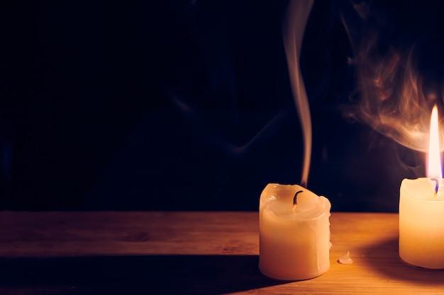나무 테이블에 굽고 꺼진 촛불. 촛불에서 나오는 부드럽고 하얀 연기. 희망과 기억의 불꽃. 군중, 피곤하거나 죽어가는 개념에서 눈에. 복사 공간이 있는 보기를 닫습니다.