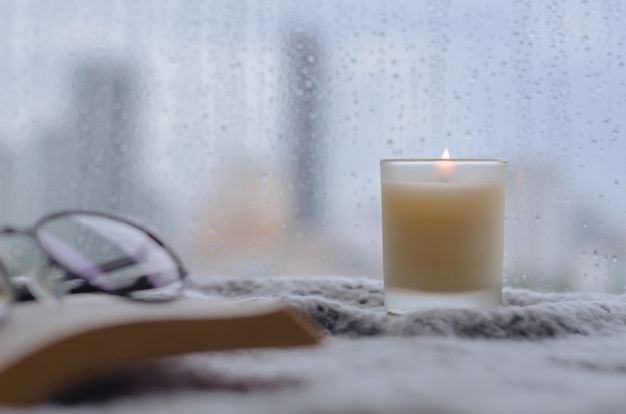 Burning aroma candle puts near by window that have rain drop in monsoon season with blurred city background. zen and relax concept.