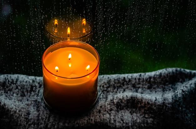 燃えるアロマキャンドルは、モンスーンの季節に雨が降る窓の近くの布でテーブルに置きます