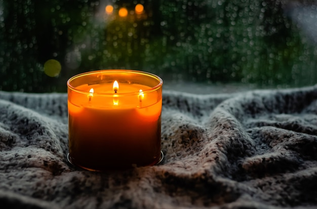 Burning aroma candle puts on table with cloth near by window that have rain drop in monsoon season