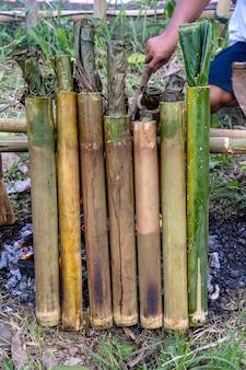 伝統的な料理、アジア料理で竹ご飯を燃やす。ウブド、バリ島、インドネシア。閉じる。竹のショットで甘いココナッツミルクともち米を燃やした