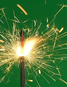 Горящая бенгальская световая палка. бенгальский огонь на зеленом фоне. вертикальный выстрел
