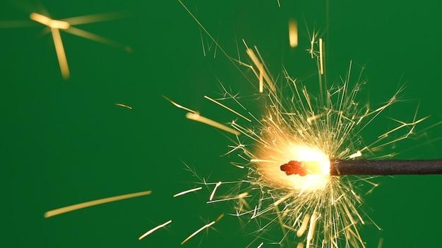 Горящая бенгальская световая палка. бенгальский огонь на зеленом фоне.