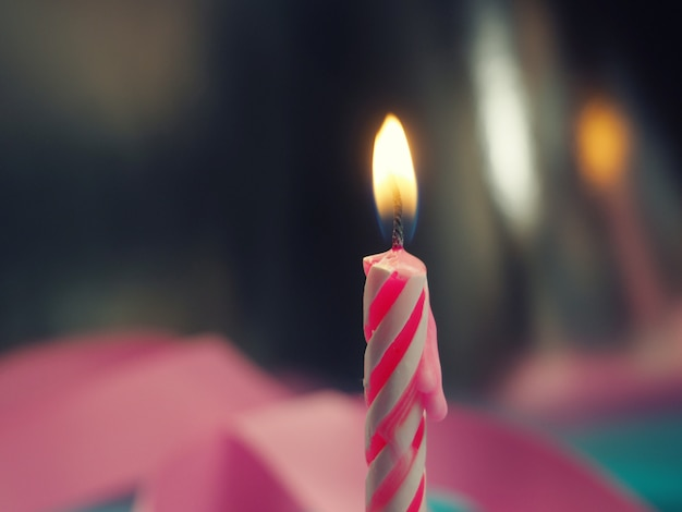 Burning birthday candle cake on a color background.