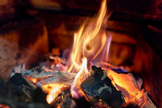 Горящие черные угли и огонь в камине