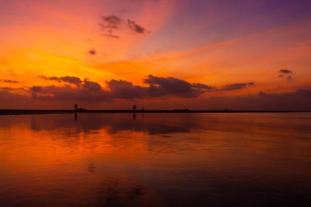Горящее яркое небо во время заката на тропическом пляже. закат во время исхода, сила людей, гуляющих по воде