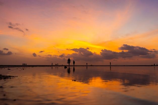 Горящее яркое небо во время заката на тропическом пляже.