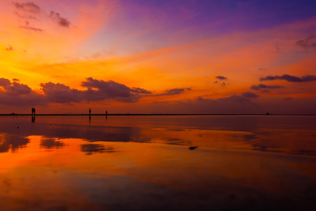Burning bright sky during sunset on a tropical beach. sunset during the exodus, the strength of people walking on water